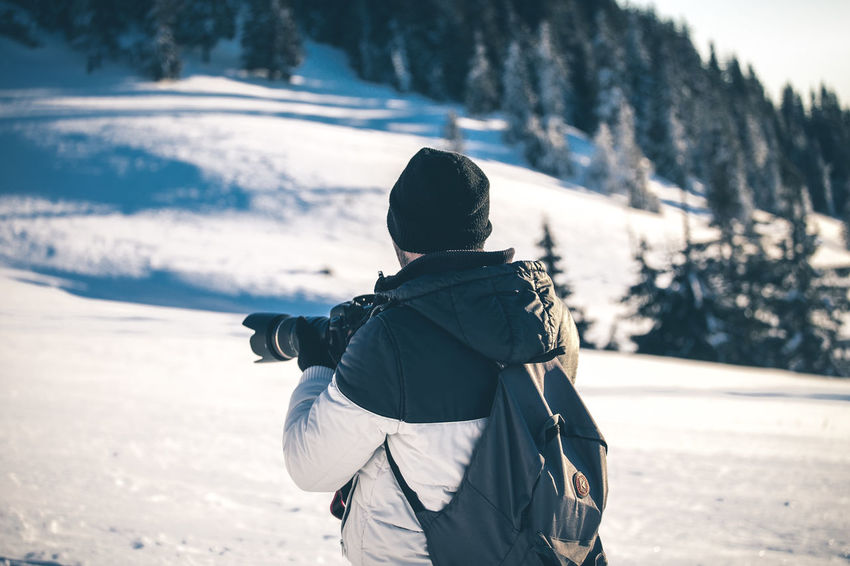 Backpack Beauty In Nature Clothing Cold Temperature Day Focus On Foreground Land Leisure Activity Lifestyles Men Nature Outdoors People Real People Rear View Snow Waist Up Warm Clothing Winter