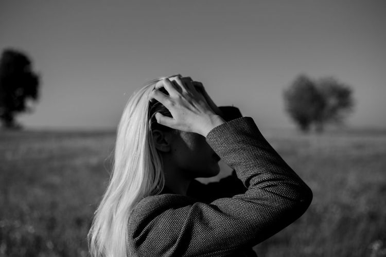 A young woman fixing her hair while standing in a field