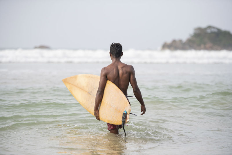 Shirtless man with surfboard wading in sea against clear sky