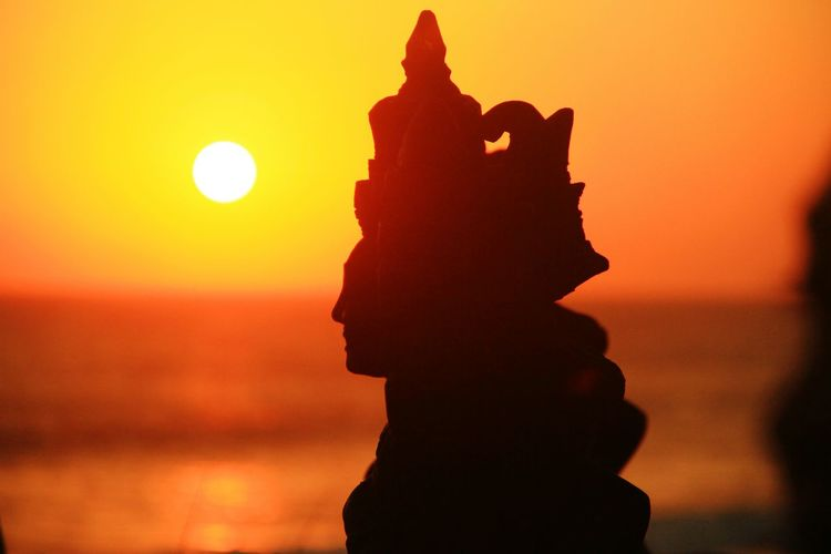 Close-up of silhouette statue against sky during sunset