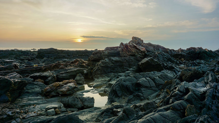 Scenic view of rocks against sky during sunset