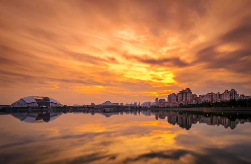 Sport hub and buildings by kallang lake against dramatic sky during sunset