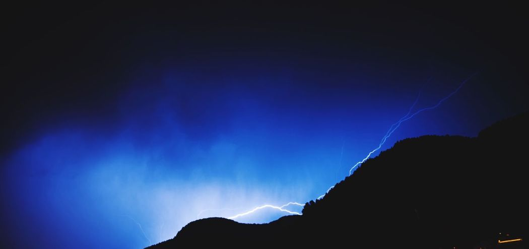 Power In Nature Blue Night Silhouette Nature No People Lightning Beauty In Nature Scenics Low Angle View Illuminated Outdoors Sky Forked Lightning Stormy Weather Storm Stormy