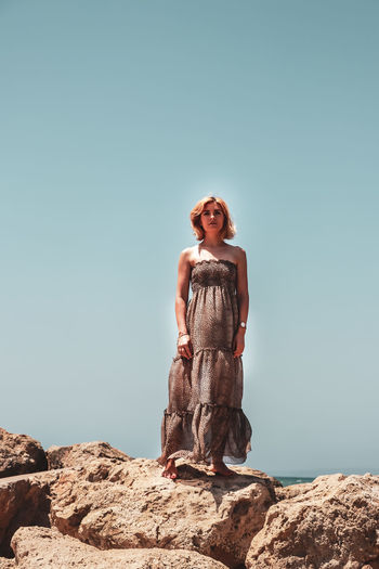 Low angle portrait of mid adult woman in off shoulder dress standing on rock at beach against clear sky during sunny day