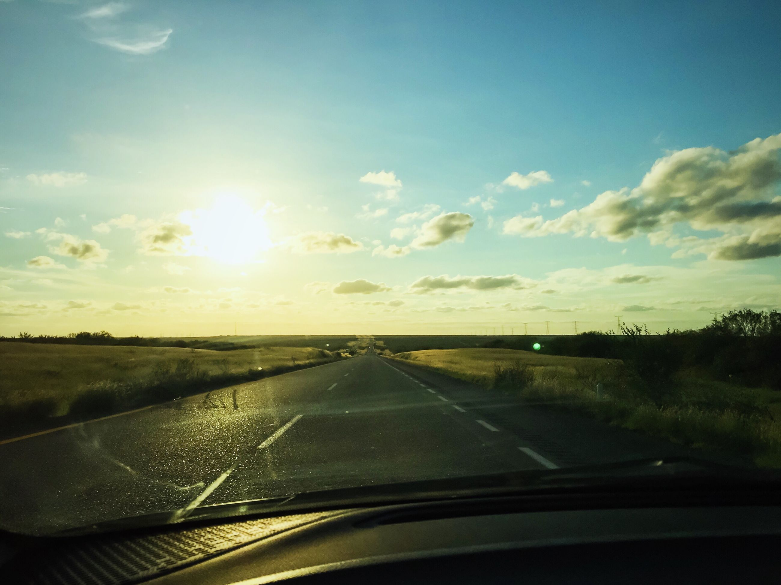 transportation, mode of transport, car, vehicle interior, land vehicle, glass - material, road, sky, windshield, car interior, transparent, landscape, part of, cloud - sky, travel, cropped, window, side-view mirror, nature, tree