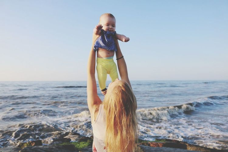 Rear view of woman playing with baby at beach against clear sky