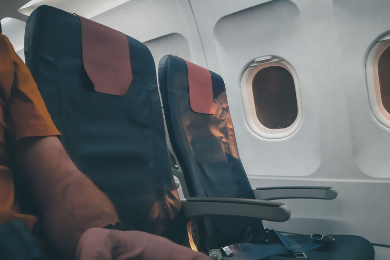 Midsection of man sitting in airplane