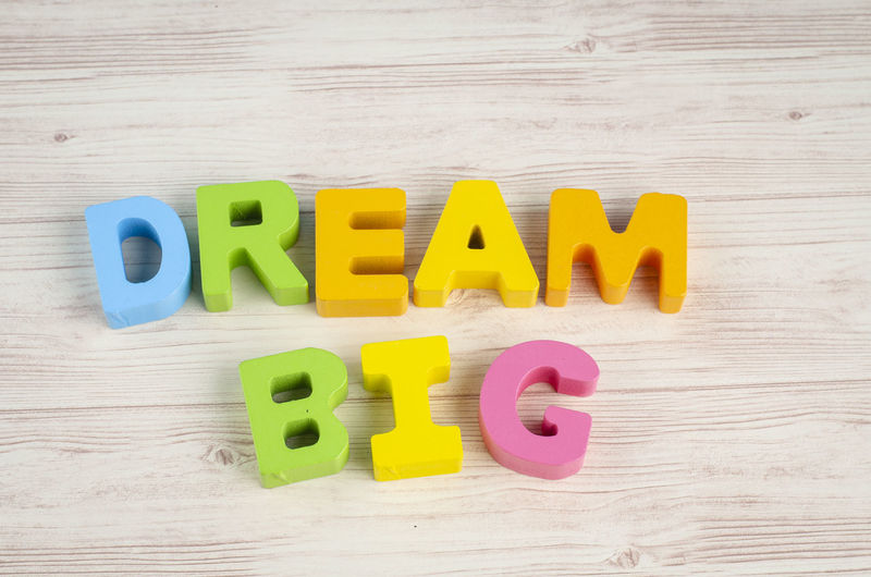 DREAM BIG word on wooden desk over blue background Text Western Script Wood - Material Capital Letter Letter Alphabet Indoors  Table Yellow Education Multi Colored Communication Still Life Childhood Directly Above Toy Learning Close-up Plastic
