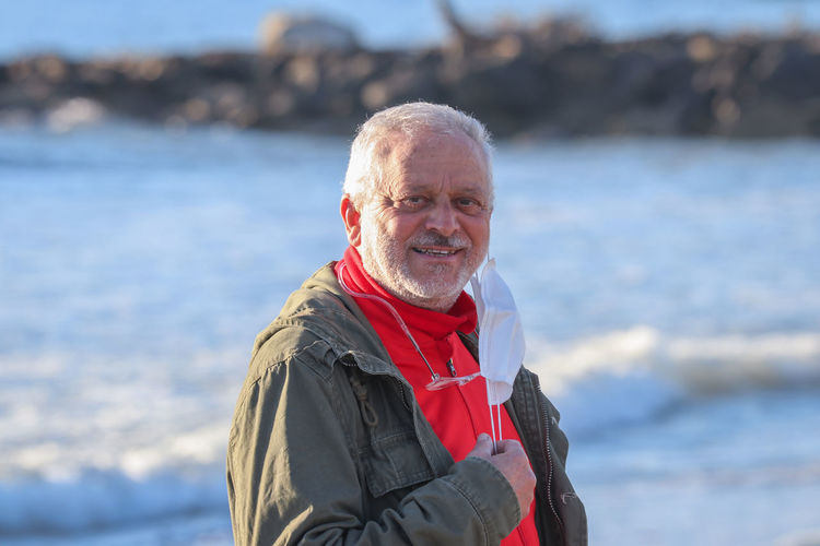 Portrait of smiling man standing against sea during winter