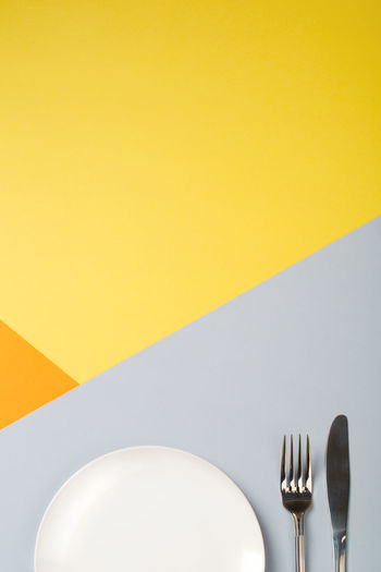 High angle view of empty plate on table against wall