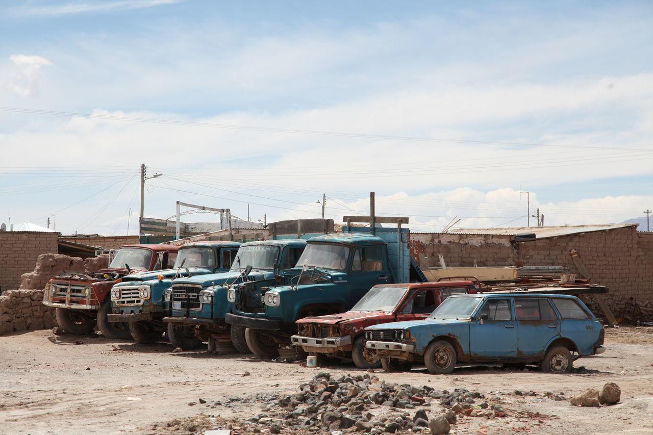 Vehicles In Junkyard Against Cloudy Sky