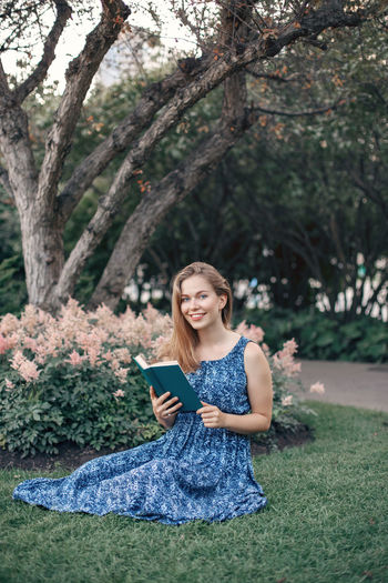 Portrait of smiling young holding book while woman sitting on grass against trees
