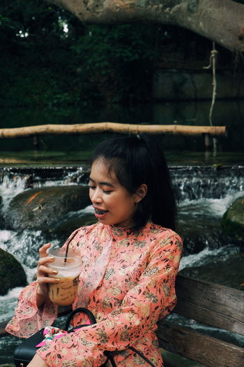 Young woman drinking coffee at riverbank