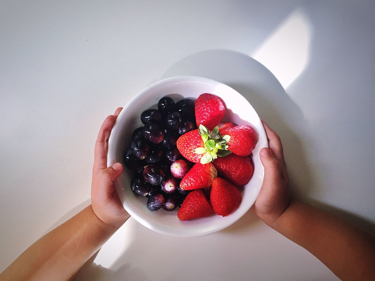 Cropped hand holding bowl of strawberries and grapes over table