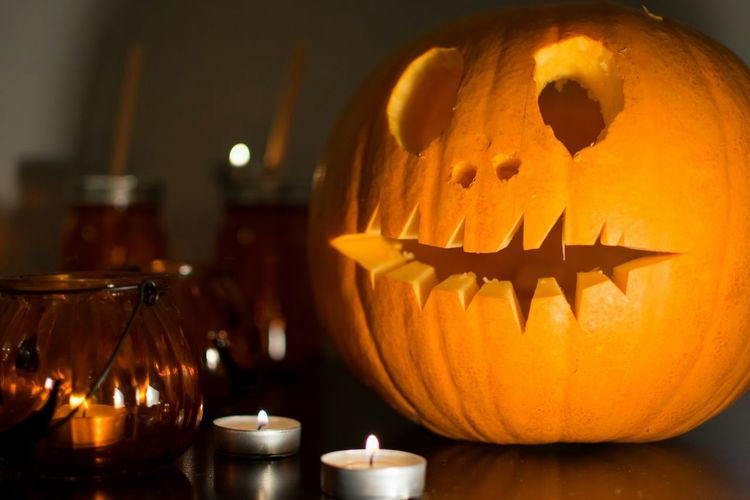Close-up of illuminated helloween pumpkin on a wooden table