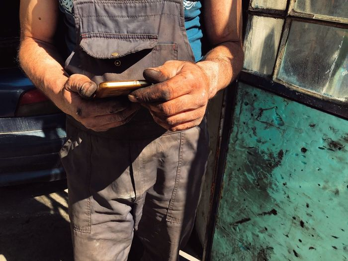 Midsection of mechanic using mobile phone at garage