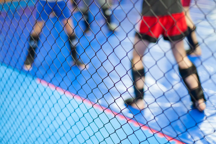 Low section of men practicing martial arts seen through chainlink fence