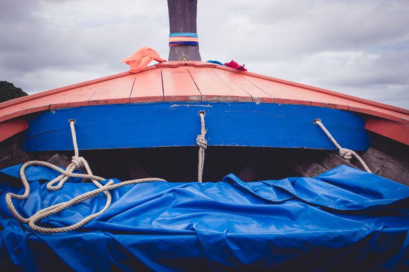 Tarpaulin on boat against cloudy sky