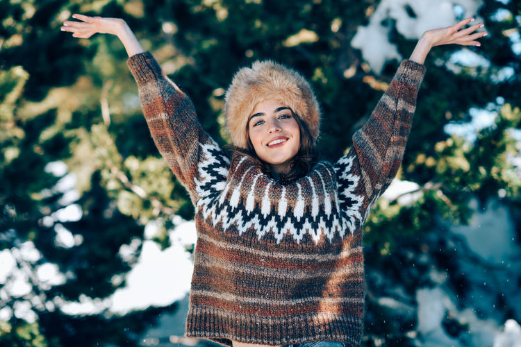 Portrait of smiling young woman with arms outstretched standing against trees during winter