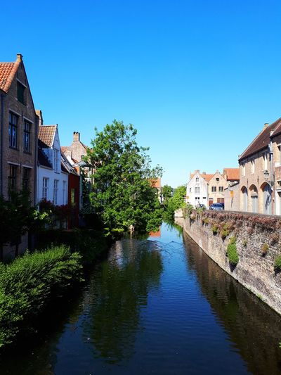 River amidst houses and buildings in old town against clear blue sky in bruges