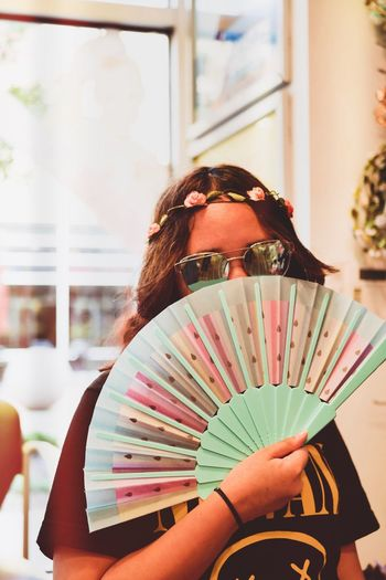 Portrait of woman in sunglasses covering face with hand fan at home