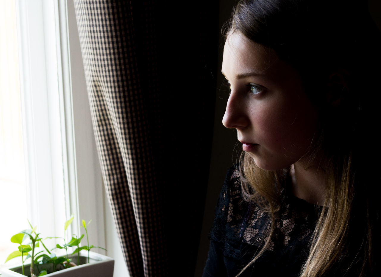 Young woman looking out through window
