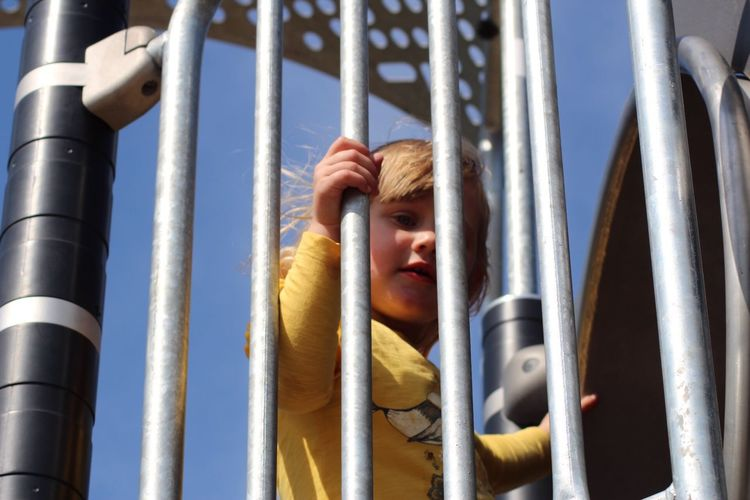 Low angle view of girl by slide at playground