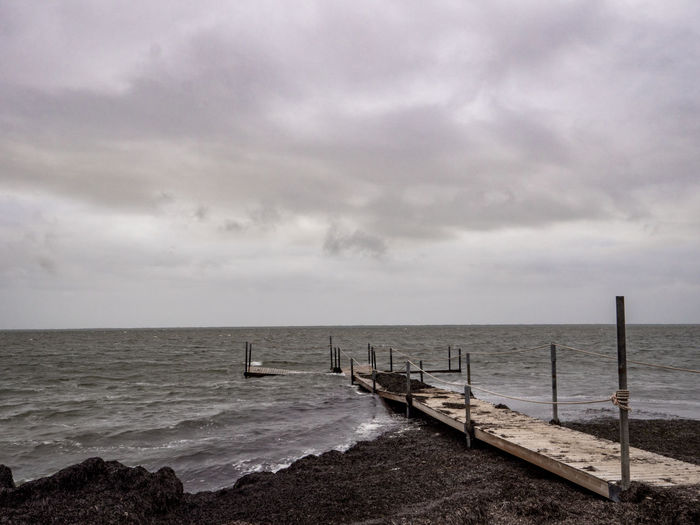 Water Cloud - Sky Sea Sky Tranquility Horizon Horizon Over Water Scenics - Nature Beauty In Nature Nature Tranquil Scene No People Outdoors Land Day Jetty Overcast Beach Ominous Wooden Post EyeEmNewHere EyeEm Best Shots EyeEm Nature Lover EyeEm Selects Enjoying Life