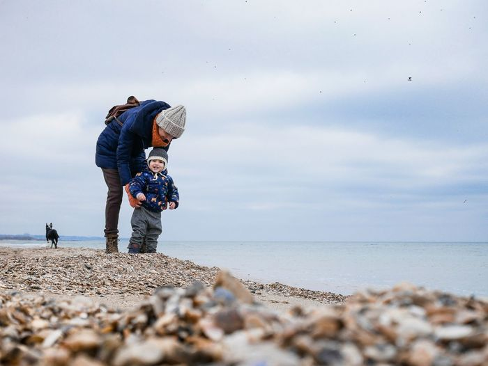 Father and son standing at beach against sky