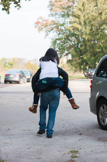 Brother Giving His Sister a Piggyback Ride Brother Carrying Family Fun Piggyback Relationship Sister Boy Carry Childhood Girl Lifestyles Mode Of Transport Outdoors People Real People Rear View Ride Walking