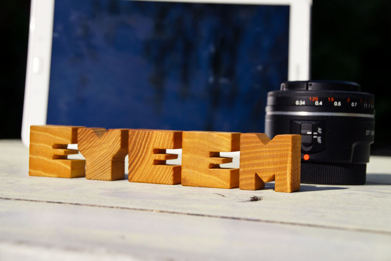Close-up of wooden eyeem text by camera lens on table