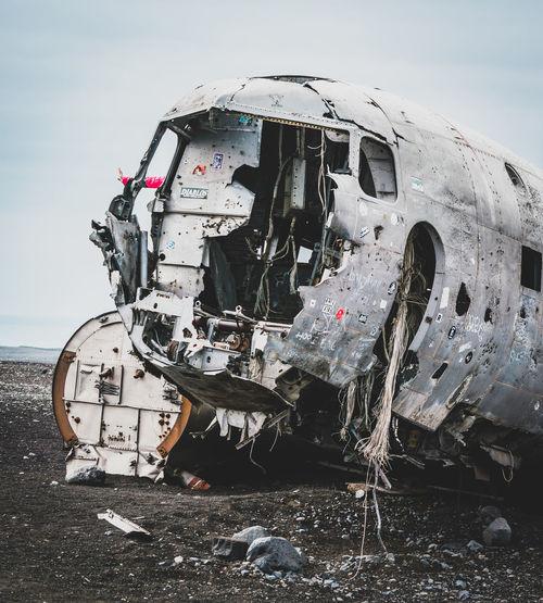 Damaged airplane on land against sky