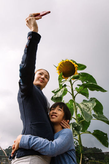 Low angle view of mother and son standing sunflower while taking selfie