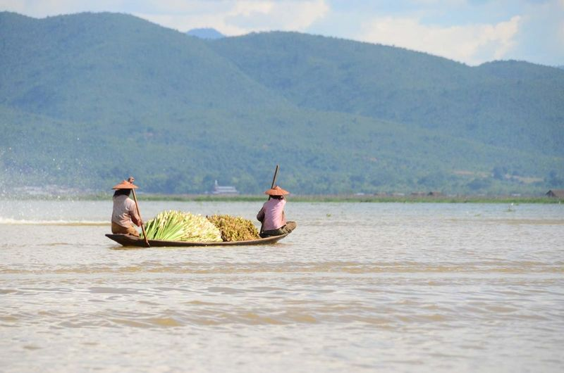 People with spring onions in boat on lake against mountains