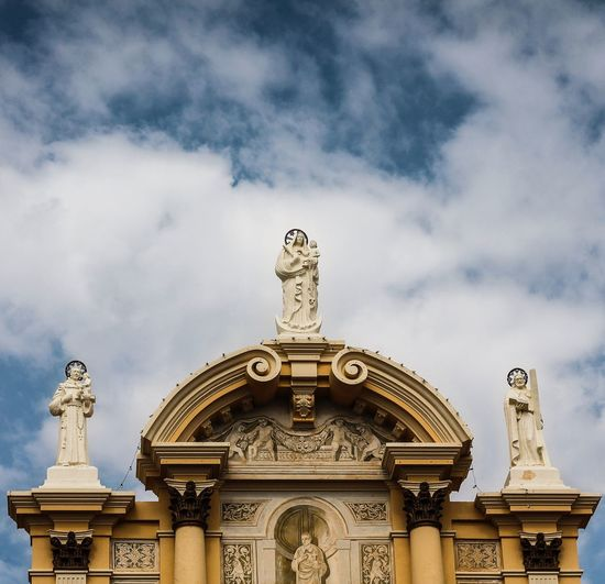 Low angle view of sculptures on historic building against cloudy sky