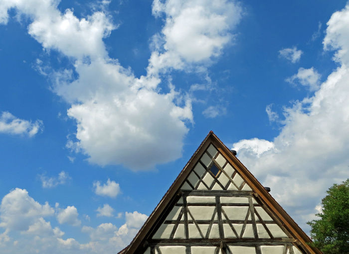 Low angle view of half-timbered house against cloudy sky