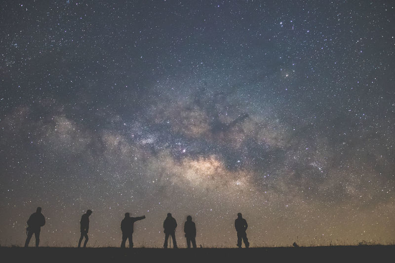 Low angle view of silhouette people standing on field against star field at night