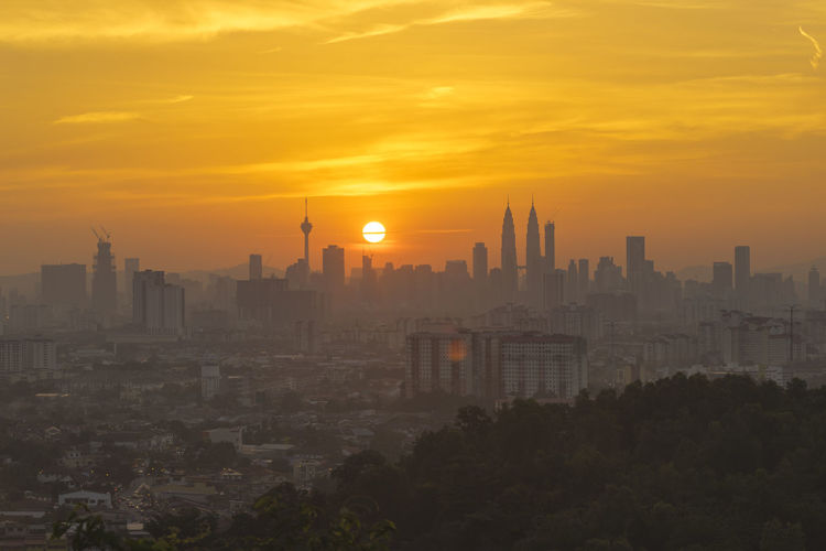 A dramatic view of Kuala Lumpur city skyline at sunset with a yolk sun and building silhouettes. Kuala Lumpur Malaysia  Landmarks Architecture Building Exterior Built Structure City Cityscape Day Downtown District Modern Nature No People Orange Color Outdoors Sky Skyscraper Sun Sunset Sunsets Travel Destinations Urban Skyline Yolk