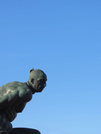 The monument Quattro Mori ( of the Four Moors ) in Livorno city . View of one of the four moors against the blue sky . Tuscany, Italy African ArtWork Bandini Bronze Four Livorno Medici Renaissance Square Statue Tacca Tuscany Art Black Chain Historic Italy Monument Moorish Moors Mori Muscle Sculpture Slave Tourism