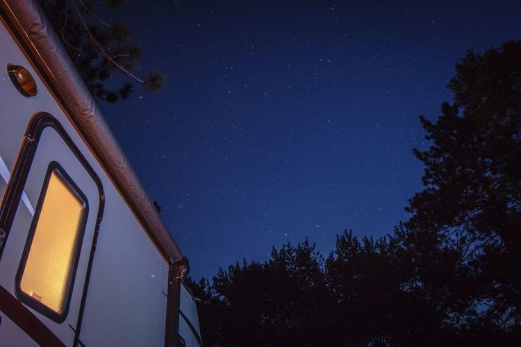 Low angle view of travel trailer against star field at night