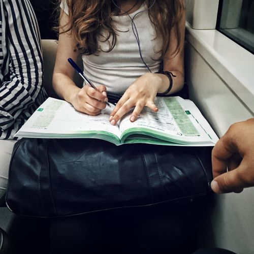 Midsection of woman studying in train