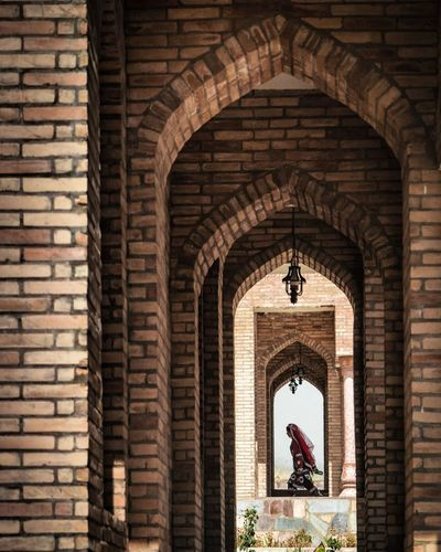 A woman walking past the arches of the Hisor Fortress in Tajikistan Dushanbe EyeEm Best Shots EyeEmNewHere Tajikistan Travel Travel Photography Arch Architecture Brick Brick Wall Building Building Exterior Built Structure Day History The Past Travel Destinations Wall Wall - Building Feature The Photojournalist - 2018 EyeEm Awards The Traveler - 2018 EyeEm Awards