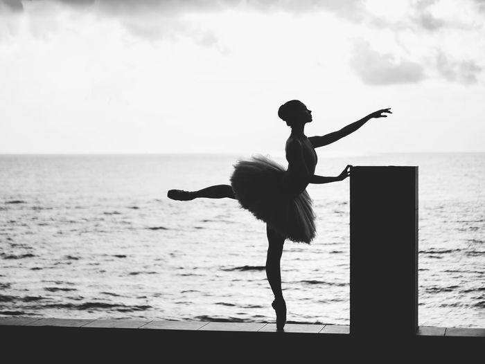 Woman ballet dancing against sea