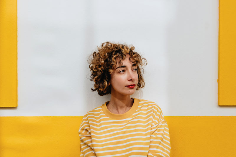 Portrait of beautiful young woman against yellow wall