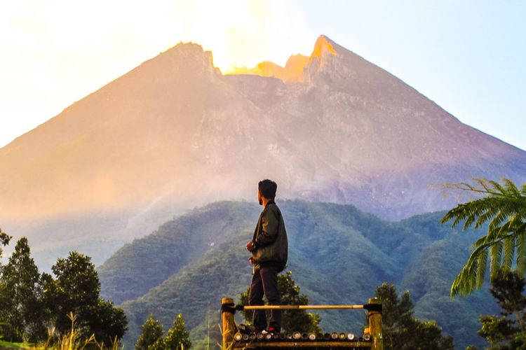 Man Standing At Observation Point Against Mountain During Sunset