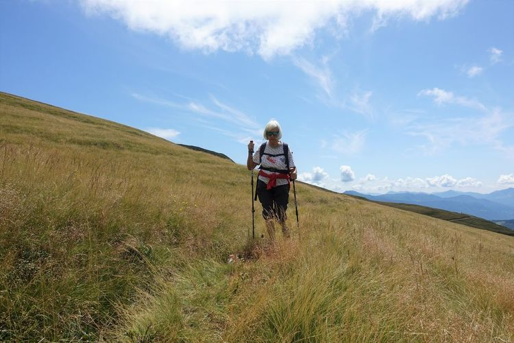 Woman hiking on mountain against sky