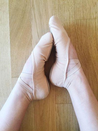 Low section of ballet dancer sitting on hardwood floor