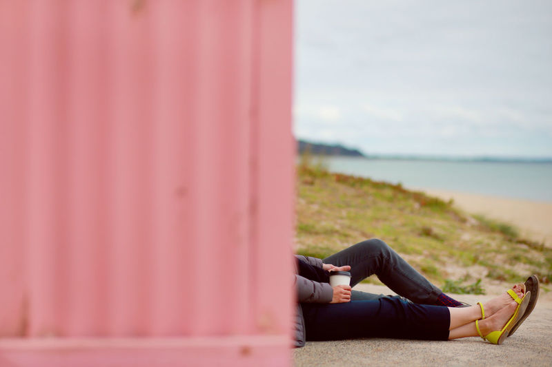 Low Section Of Couple With Coffee Cup While Sitting By Wall At Beach