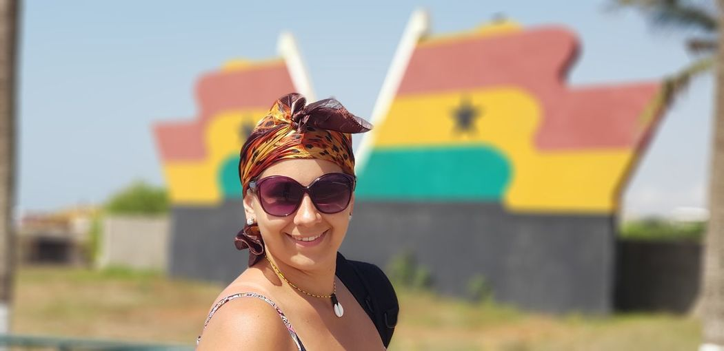 Side view portrait of smiling woman wearing sunglasses against ghanaian flag