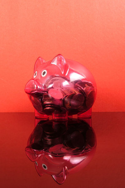 Saving concept with red piggy bank on red background. Piggy Bank Animal Representation Art And Craft Close-up Coin Colored Background Conceptual Photography  Container Glass - Material High Angle View Indoors  Investment No People Pink Color Red Red Background Representation Saving Concept Shape Shiny Still Life Studio Shot Table Transparent Wall - Building Feature
